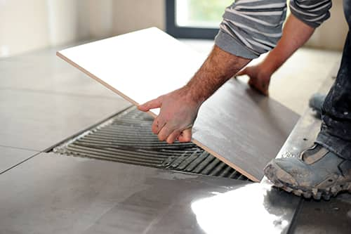 Person installing a tile floor